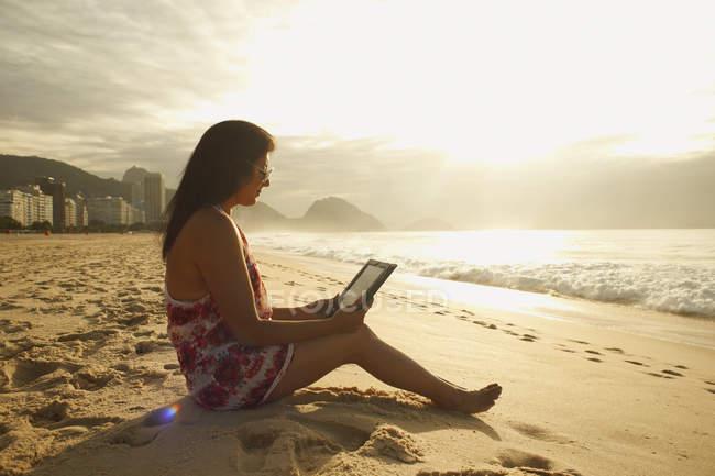 Mulher madura olhando tablet digital na praia de Copacabana, Rio De Janeiro, Brasil — Fotografia de Stock