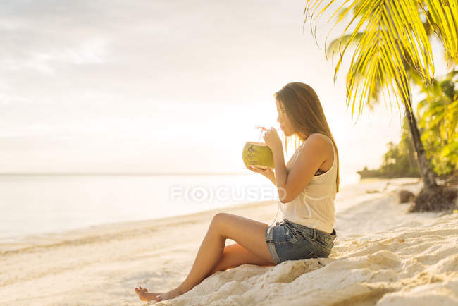 Young woman drinking fresh coconut milk on Anda beach, Bohol Province, Philippines — Stock Photo