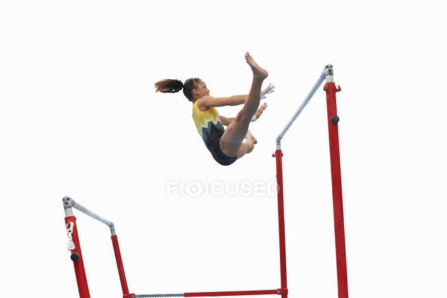 Young gymnast performing on uneven bars — Stock Photo