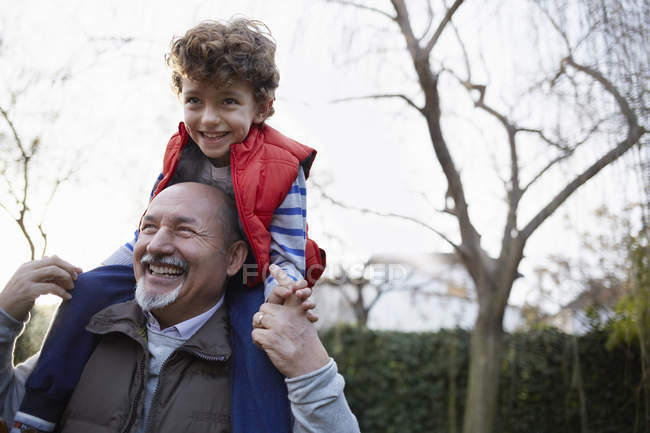 Mature man carrying grandson on shoulders smiling — Stock Photo