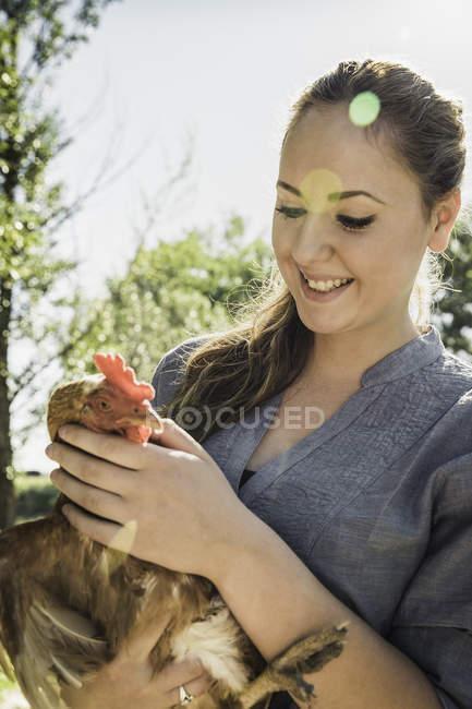 Жінка холдингу курка, дивлячись вниз посміхається — стокове фото