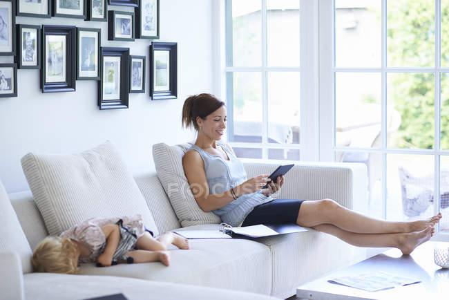 Mid femme adulte à l'aide de tablette numérique sur le canapé du salon, tandis que la fille de bébé dort — Photo de stock