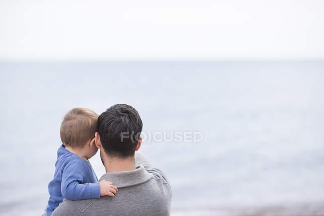 Pai e filho novo olhando para a vista para o mar, vista traseira — Fotografia de Stock