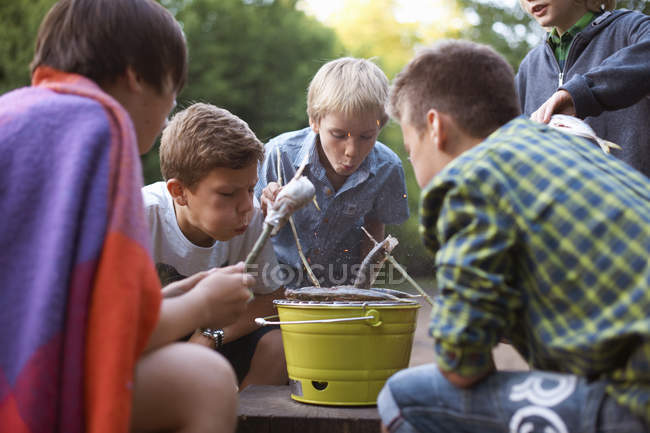 Little boys cooking fish over barbecue — Stock Photo