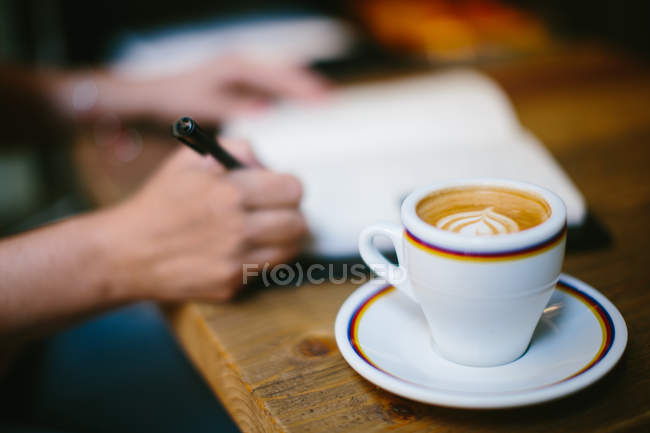 Coffee cup on table and womans hands writing in notebook — Stock Photo