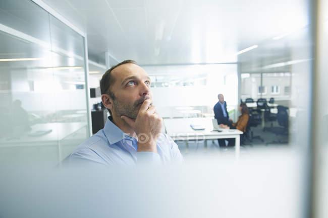 Homme pensant à l'intérieur de bureau, personnes à l'arrière-plan — Photo de stock