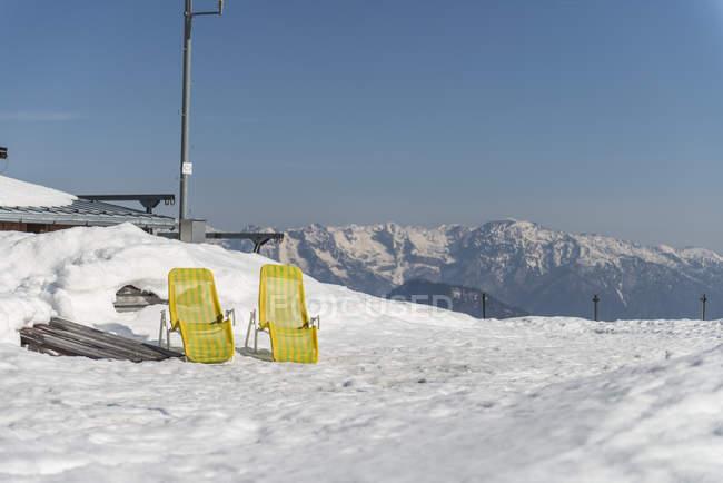 Deux chaises longues jaunes sur neige — Photo de stock