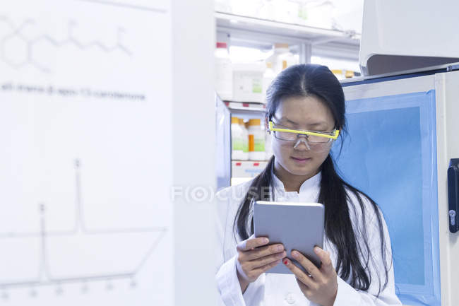 Female scientist reading digital tablet in laboratory — Stock Photo