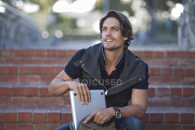 Homem adulto médio tomando laptop de mochila nos degraus da cidade — Fotografia de Stock