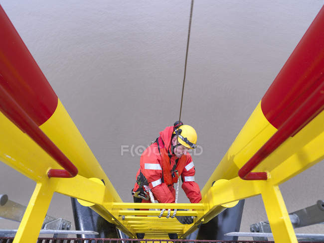Offshore windfarm worker climbing turbine, high angle view — Stock Photo