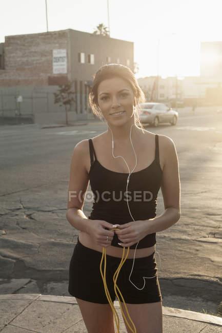 Retrato de mujer joven, usando auriculares, llevar ropa deportiva - foto de stock