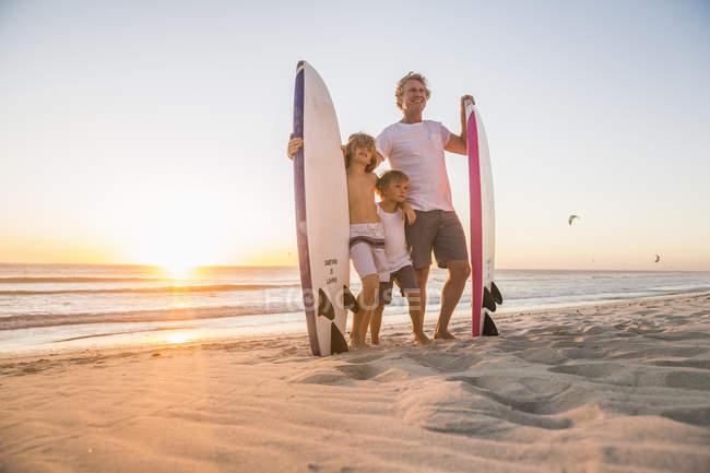 Vista do comprimento total do pai e filhos em pé na praia, segurando a prancha ao pôr do sol — Fotografia de Stock