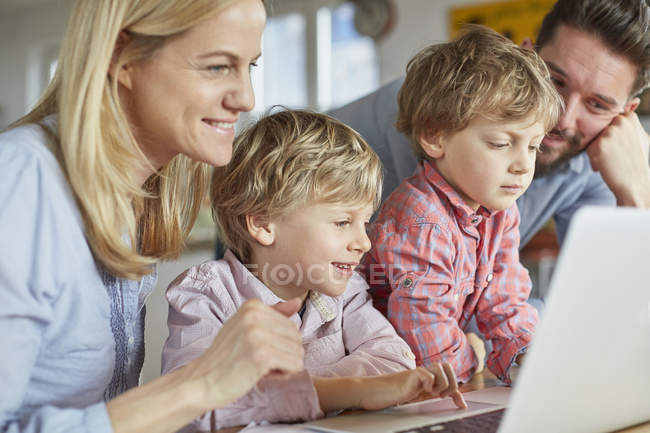 Parents and sons using laptop — Stock Photo
