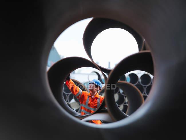 Uomo che controlla i tubi in fabbrica — Foto stock