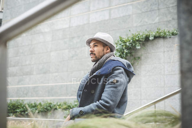 Portrait of man in coat and hat looking away — Stock Photo