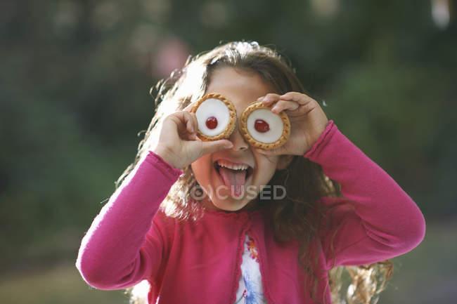 Портрет девушки с Тарталетки ее глазах в саду — стоковое фото