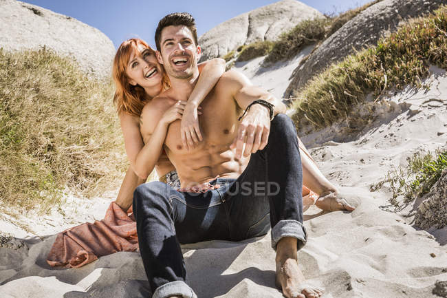 Couple assis sur la plage, au bord des rochers, embrasser, rire — Photo de stock