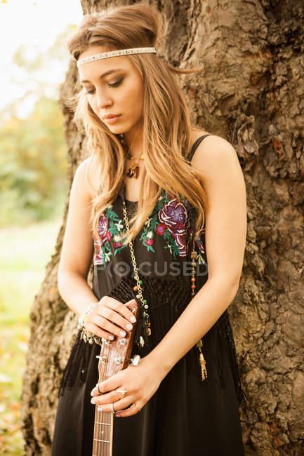 Хіпі жінка з гітарою дивитися сумно стоячи на дерево — стокове фото