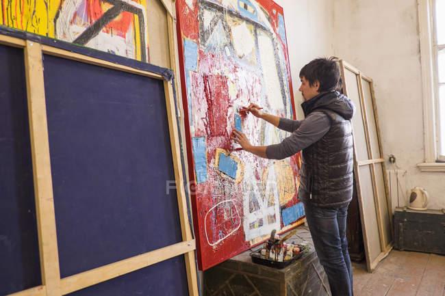 Künstler zeichnet abstrakte Malerei im Atelier — Stockfoto