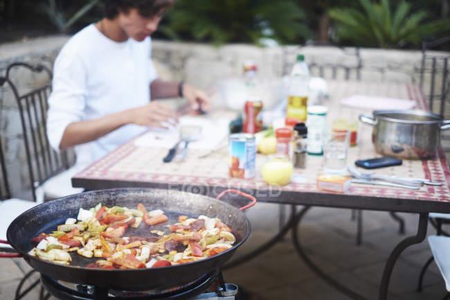 Giovane che mangia mescolare pranzo fritto al tavolo patio — Foto stock