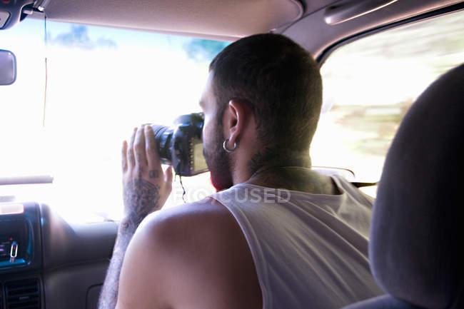 Jovem tirando fotografias através do pára-brisas do carro — Fotografia de Stock