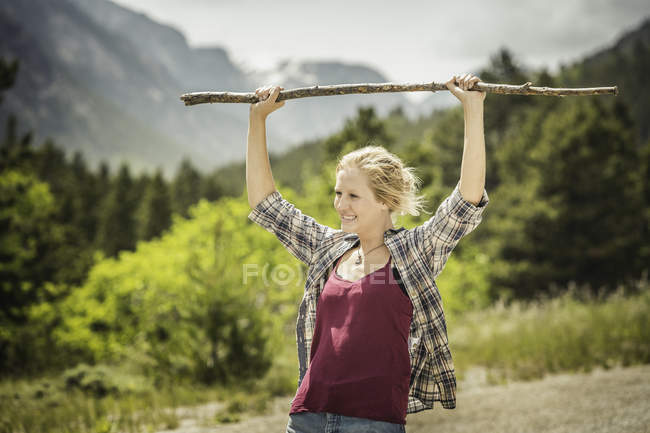 Teenage girl hiker holding up walking stick on rural road, Red Lodge, Montana, USA — Stock Photo