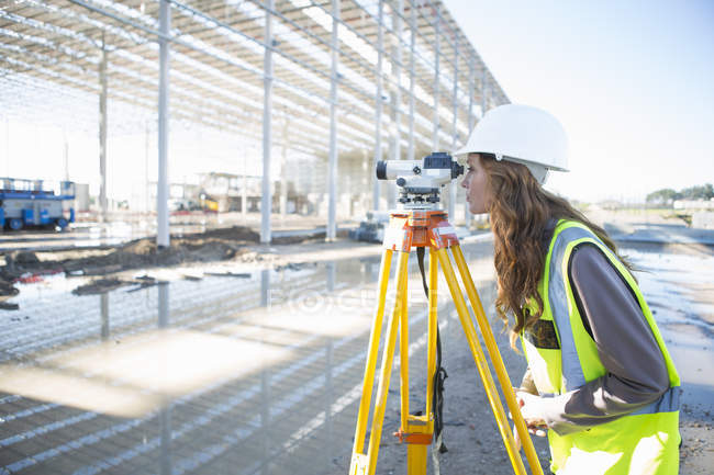 Геодезист, наклонившись вперед смотреть через уровень на строительной площадке — стоковое фото