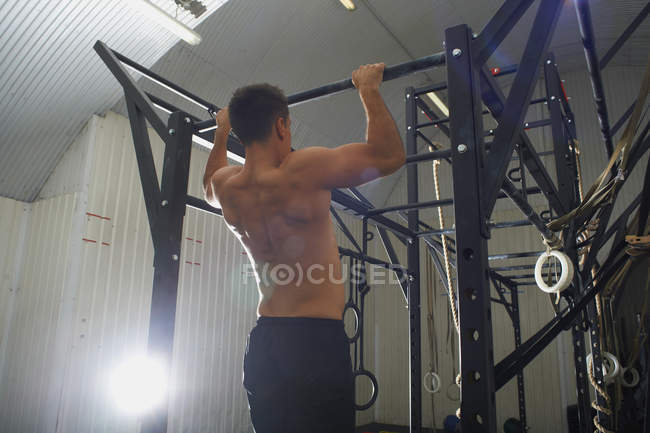 Man doing pull ups in gym, rear view — Stock Photo