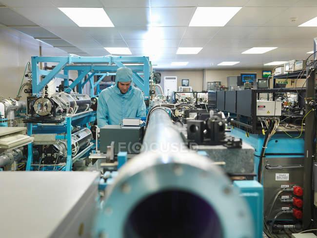 Cientista masculino vestindo roupas protetoras trabalhando com laser em laboratório — Fotografia de Stock