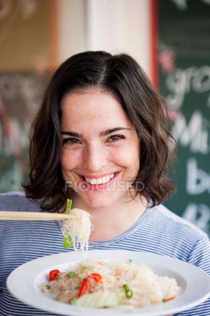 Mulher segurando macarrão com pauzinhos e sorrindo — Fotografia de Stock