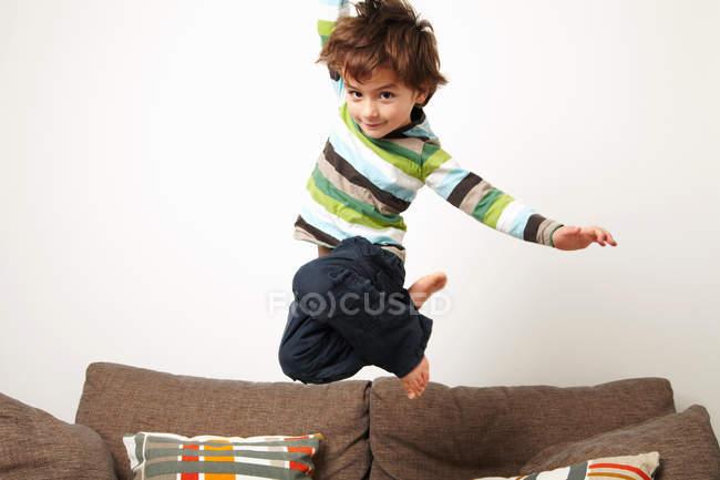 Молодий хлопчик, стрибати на дивані — стокове фото