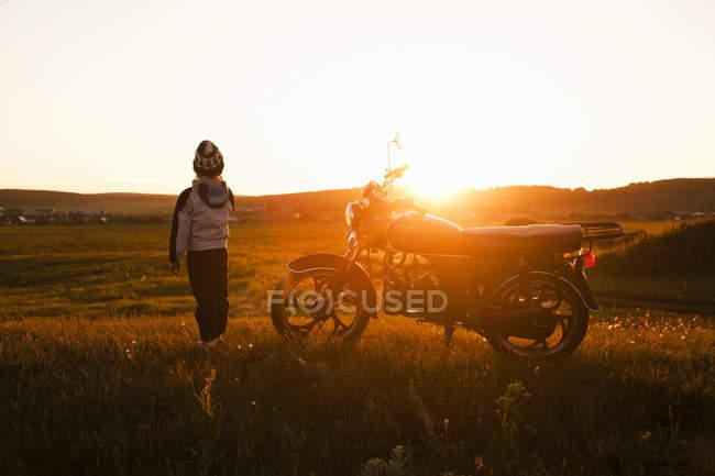 Вид сзади мальчик и мотоцикла на закате, Sarsy деревне, Свердловская область, Россия — стоковое фото
