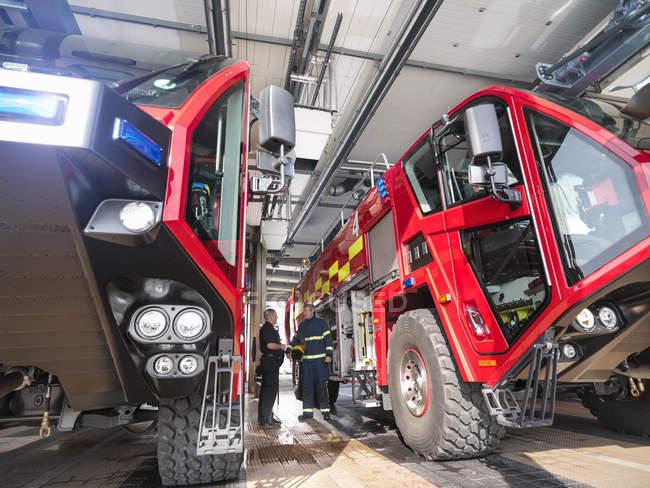 Пожежник в обговоренні пожежних машин в аеропорту пожежна станція — стокове фото