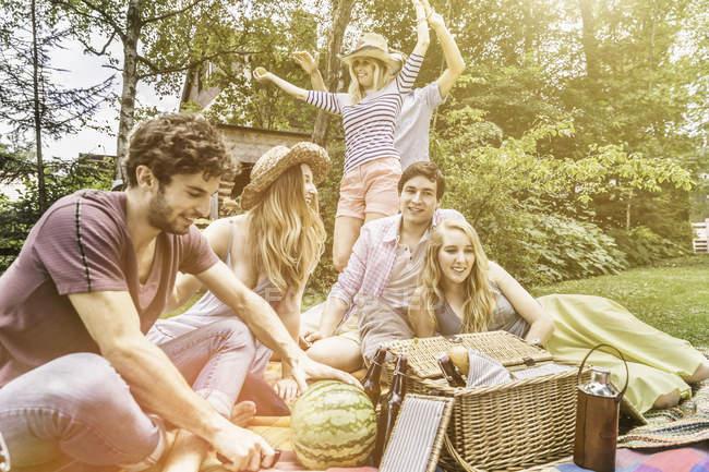 Männliche und weibliche Freunde picknicken im Garten — Stockfoto