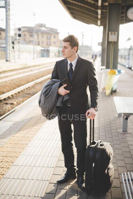 Молодий підприємець приміських стоячи на залізничні платформи з чемодан. — стокове фото