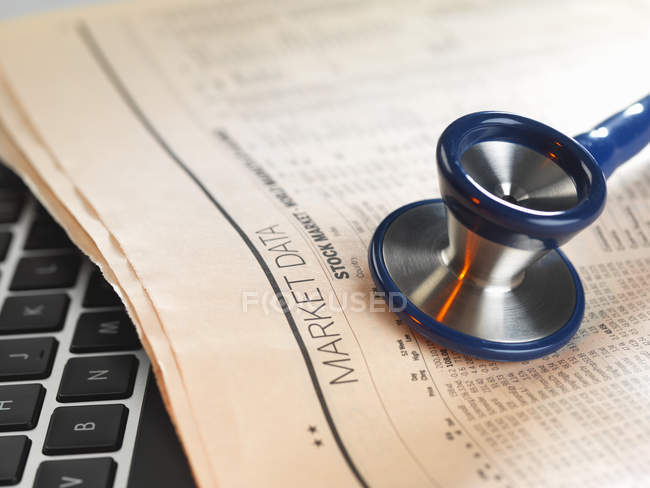 Stethoscope on newspaper with financial markets for investing — Stock Photo