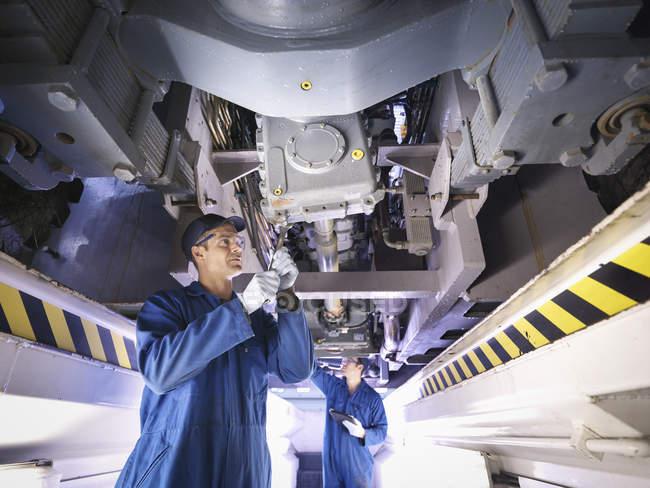 Engineers underneath truck in repair factory — Stock Photo