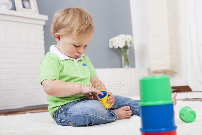 Niño jugando con juguetes de plástico - foto de stock
