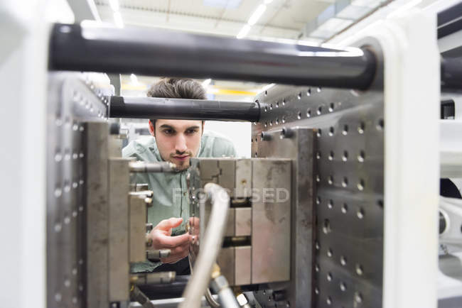 Male worker using machinery at tool manufacturing plant — Stock Photo