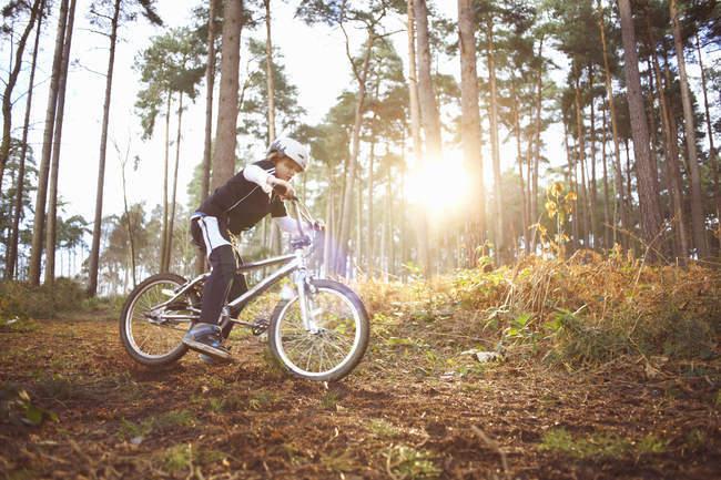 Boy riding his BMX through forest — Stock Photo