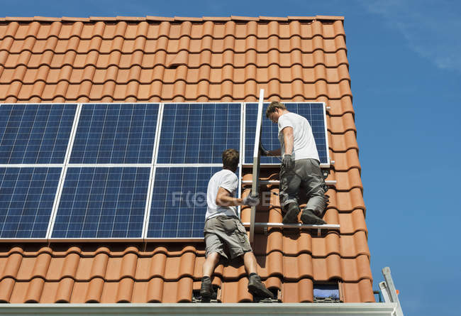 Workers installing solar panels on roof framework of new home, Netherlands — Stock Photo