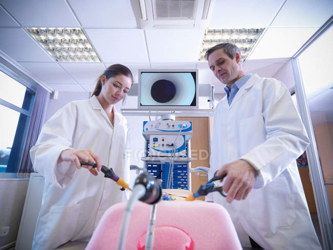 Male and female scientists use a medical simulator for training — Stock Photo