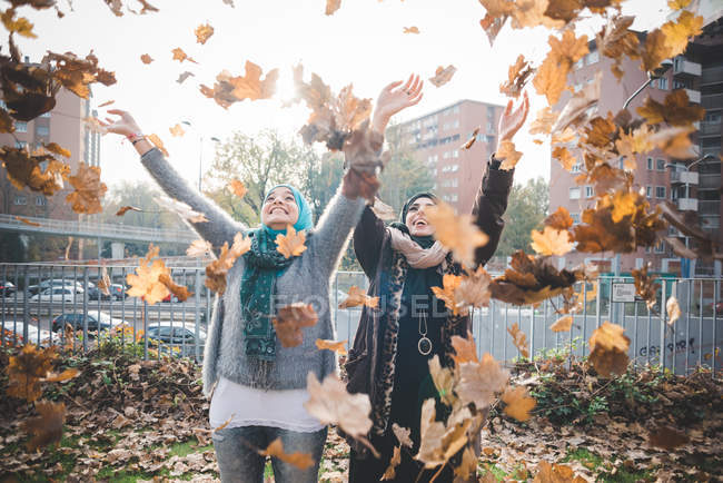 Two young women in park throwing autumn leaves — Stock Photo