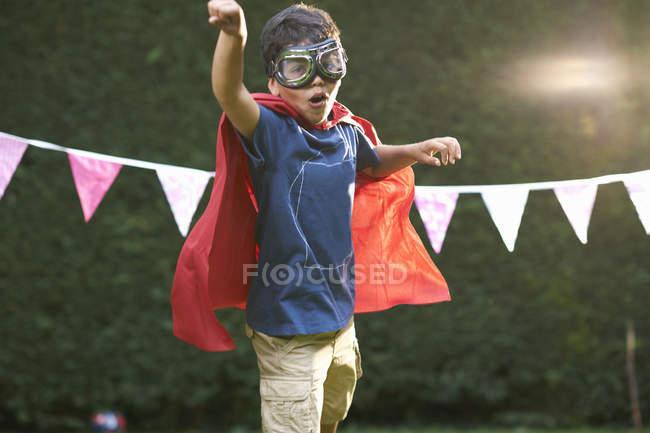 Хлопчик, носити захисні окуляри і мис в супергероя позицію — стокове фото
