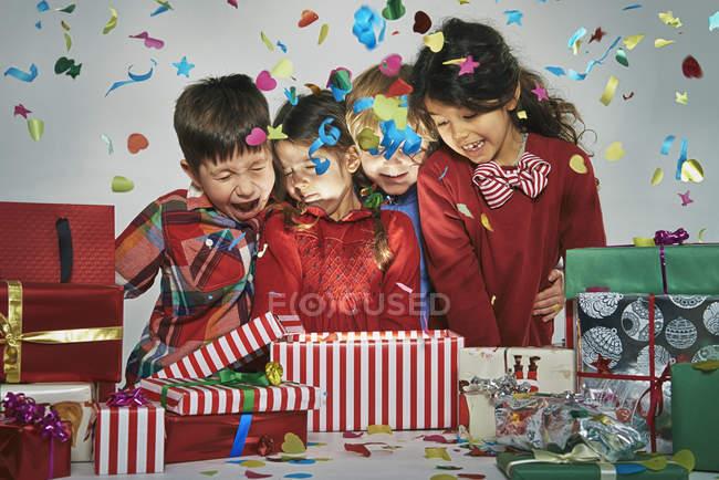 Удивлённые братья и сёстры разворачивают сверкающую рождественскую коробку с конфетти. — стоковое фото