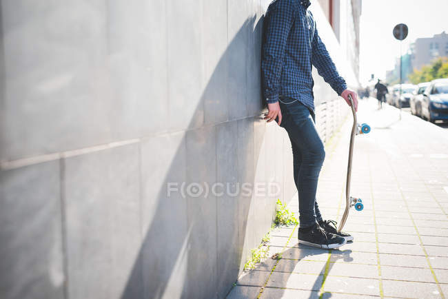 Young male urban skateboarder leaning against sidewalk wall — Stock Photo