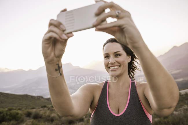 Mujer de tamaño grande en la montaña usando smartphone para tomar selfie sonriendo - foto de stock