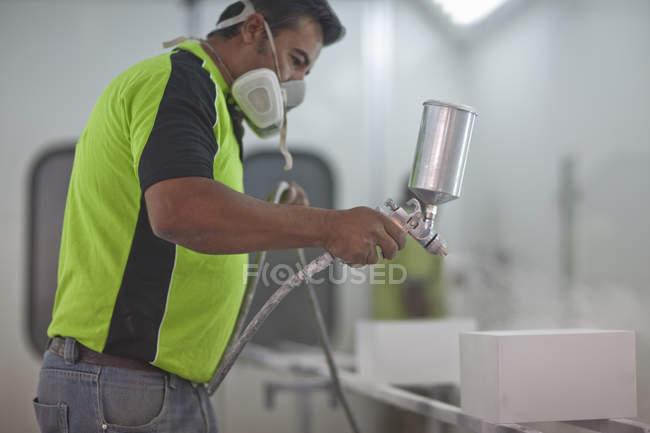 Homem pulverização de produtos de madeira na oficina carpinteiros — Fotografia de Stock