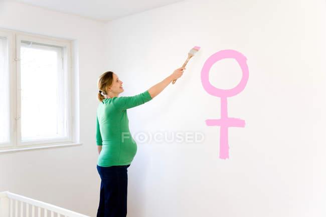 Donna incinta pittura vivaio — Foto stock