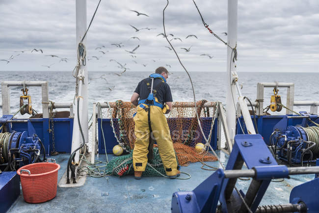 Fisherman inspecting trawl net on research ship — Stock Photo